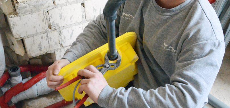 Sanitärinstallateur bei der Duschsanierung mit Bodenablaufpumpe